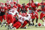 A group of Fresno State defensive players take down one of their running back teammates in defensive drills at Wednesday