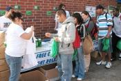 Maira De La O (left) hands out T-shirts and energy-efficient Energy Star light bulbs to students in front of the University Center Nov. 13 for the ongoing Go Green campaign. The conservation project lasts the whole month of November. De La O and other students participated in the campaign as part of their Public Relations Cases and Campaigns class.