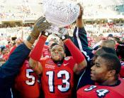 Fresno State wide receiver Jason Crawley and his teammates hold up the Humanitarian Bowl trophy after defeating Georgia Tech. The university received a payout of $478,000 for participating in the bowl game.