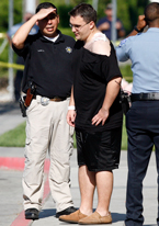 Drew Pfeiff, a plaintiff in the lawsuit, is accompanied by law enforcement officials after being shot in the shoulder by Jonquel Brooks at University Village on May 7, 2007.