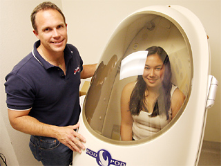 Associate professor of exerise physiology Mike Coles, Ph.D. (left), and his assistant Cory Mikuni (right) use the Bod Pod to administer body fat composition tests to students.