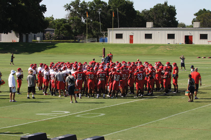 The football team gathers for a post practice speech from head coach DeRuyter on Aug. 23.  The depth chart for positions will be finalized this week. Dalton Runberg / The Collegian