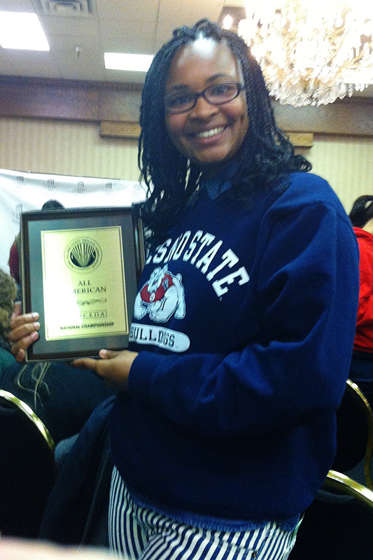 Fresno State's Candis Tate holds one of the many awards earned by the debate team. Photo Courtesy of Fresno State Department of Communication
