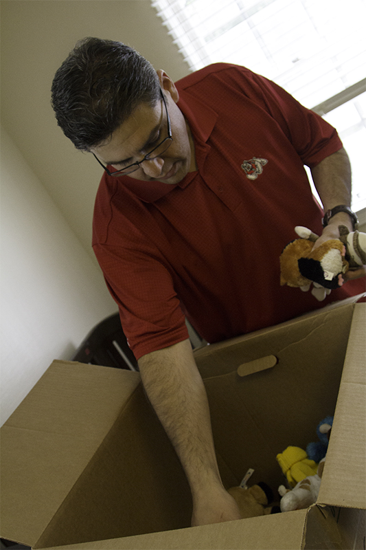 Fresno State President Joseph Castro unpacks his two-year-old son's toys in their new home on Saturday.