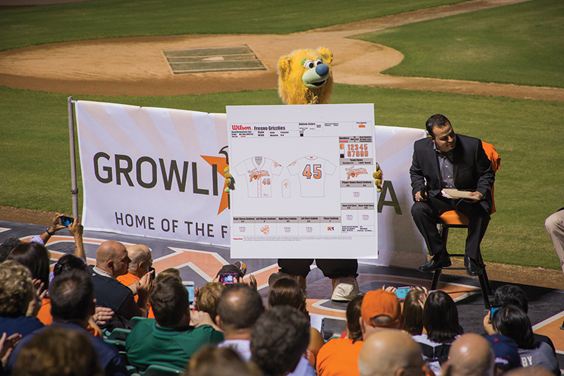 Fresno Grizzlies mascot Parker the Bear holds up a board featuring the team's new uniform and logo designs during the meet-and-greet at Chukchansi Park Thursday. Photo by Darlene Wendels/The Collegian
