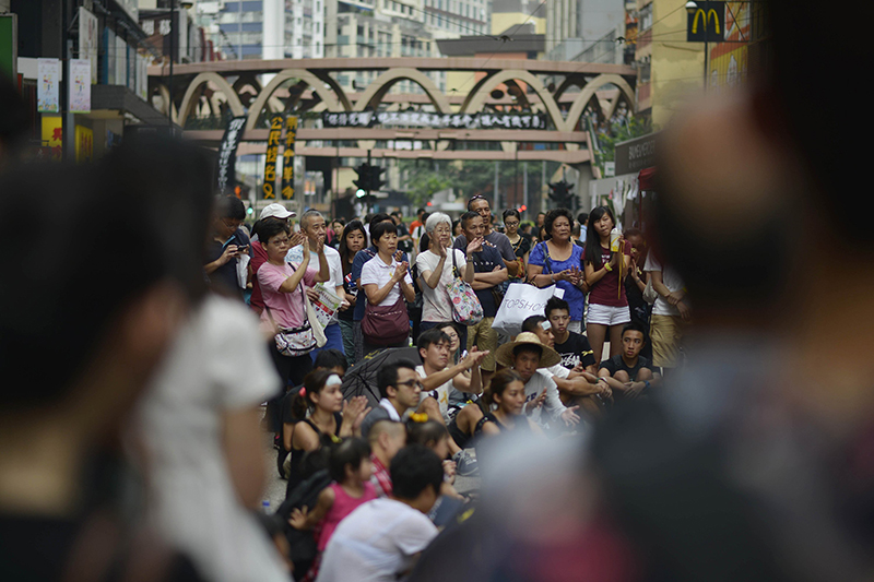 Although the crowds appear to be thinning, many people still are gathered at major points around Hong Kong, such as here in the Causeway Bay shopping district, to listen to speeches in China on Oct. 2, 2014. (Chris Stowers/Tribune News Service)