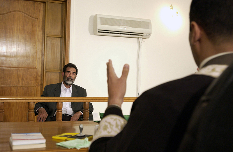 Former and deposed President of Iraq, Saddam Hussein, sits before an Iraqi judge at a courthouse in Baghdad, Iraq, where he has his initial interview to inform him of what he is being investigated for and his legal rights read to him on July, 2004. (Staff Sgt. D. Myles Cullen/U.S. Air Force)